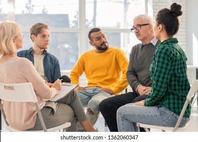 Group of multi-ethnic people of various ages sitting in circle during psychological session and interacting