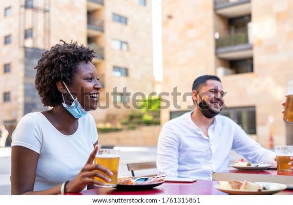 a group of multi-ethnic people who drink a beer, talk and laugh in a protective way, social distancing and drink safely, wearing a mask under the chin, focus on black woman