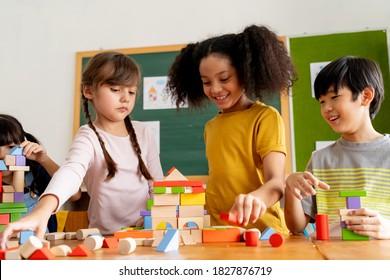Group of multiethnic school friends using toy blocks in classroom, education, learning, teamwork. Children playing with wooden blocks in classroom