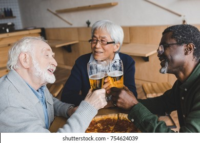 group of multiethnic senior friends clinking glasses of beer in bar with pizza on table