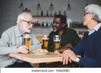 group of multiethnic senior friends drinking beer in bar
