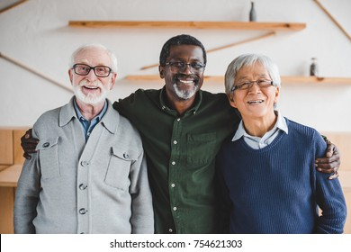 group of multiethnic senior friends embracing and looking at camera
