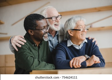 group of multiethnic senior friends embracing and looking away