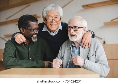 group of multiethnic senior friends embracing in bar