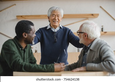 group of multiethnic senior friends meeting in cafe