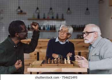group of multiethnic senior friends playing chess at cafe