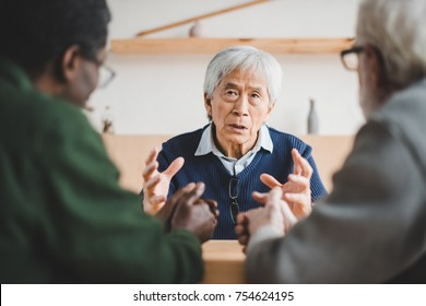 group of multiethnic senior friends spending time together and sharing stories from past