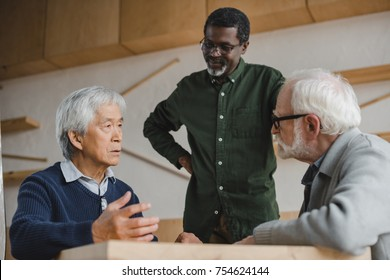 group of multiethnic senior men talking in cafe