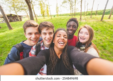 Group of multiethnic teenagers taking a selfie at park. Two boys and one girl are caucasian, one boy and one girl are black. Friendship, immigration, integration and multicultural concepts.