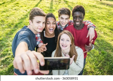 Group of multiethnic teenagers taking a selfie at park.