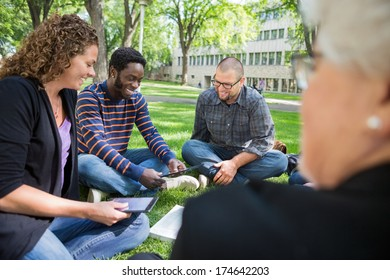 Group of multiethnic university students using digital tablet on campus park