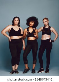 Group of multi-ethnic women in sportswear standing together over grey background. Three women of different race, figure type and size in fitness clothing.
