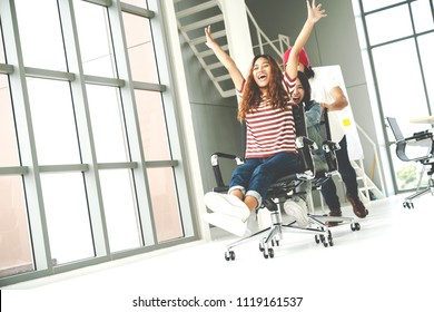 Group of multiethnic young creative teamwork having fun laughing and smiling in office chairs pushing. Coworker celebrating for success feeling happy, enjoy and excited in modern office workplace.