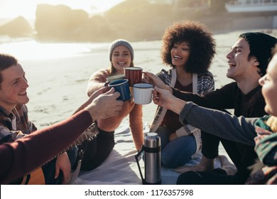 Group of multi-ethnic young people toasting coffee mugs on the beach. Group of friends spending time together at the beach having coffee.