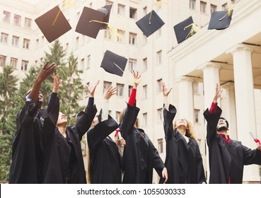 A group of multietnic students celebrating their graduation by throwing caps in the air. Education, qualification and gown concept.