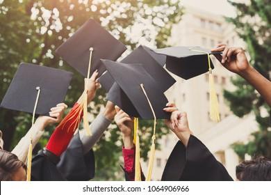 Een groep multietnische studenten vieren hun afstuderen door caps in de lucht close-up te gooien. Onderwijs, kwalificatie en toga concept.
