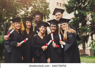 A group of multietnic students hugging on their graduation. Education, qualification and gown concept.