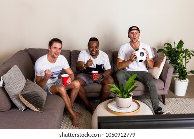 Group of multinational guys watching football on TV with excitement from couch