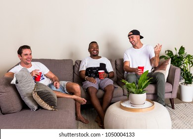 Group of multinational guys watching TV from couch