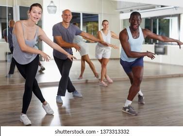 Group of multinational happy adult people enjoying active dance movement in modern studio