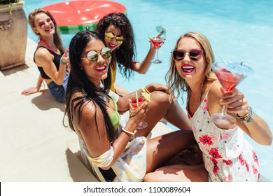 Group of multiracial female friends on summer vacation relaxed by the pool and having cocktails. Girls enjoying a poolside party with drinks.