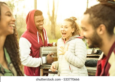 Group of multiracial friend couples having fun time out at park in autumn winter time - Youth friendship concept with people together outdoors - Focus on blond young woman - Warm contrasted filter