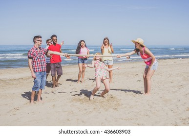 Group of multiracial friends dancing limbo at beach