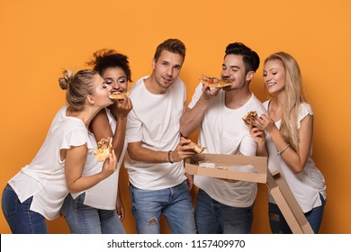Group of multiracial friends eating pizza and having fun together.