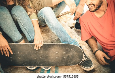 Group of multiracial friends having fun and spending time together at skate board park  - Youth friendship concept with young people sharing skateboard outdoors - Vintage retro desaturated filter