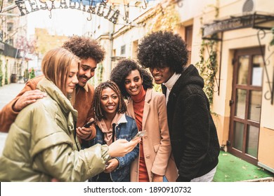 Group of multiracial friends outdoor looking at mobile phone and smiling. Mixed race students having fun together using new smartphone technology.