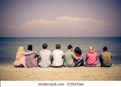 Group of multiracial friends sitting on the beach and looking at horizon - Young students on a summer vacation