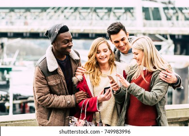 Group of multiracial friends using mobile smart phone in the city during best friends meeting - Young hipster people addicted by smartphone on social network community by posting - Technology concept