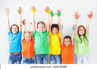 Group of multiracial funny children. Funny kids hands up.