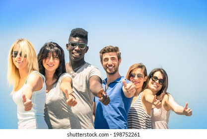 Group of multiracial happy friends together with thumbs up - Concept of international friendship and success against racism and multiethnic social barriers