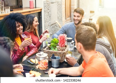 Group of multiracial people having break together in a coffee shop drinking coffee, cappuccino and fruit juice. Different culture youth integration concept.