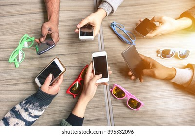 Group of multiracial people having fun together with smartphones - Closeup of hands social networking with mobile cellphones - Technology and phone addiction concept - Main focus on bottom hands