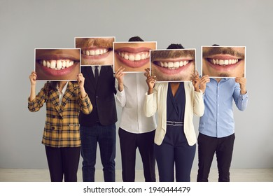 Group of multiracial people standing in studio and hiding faces behind big funny mismatched closeup photos of happy positive attractive smiles. Humour, joke, clean teeth, successful dental care result
