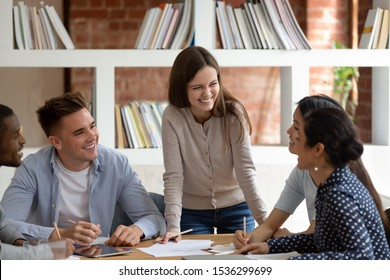 Group of multiracial student listen caucasian girl team leader do common task thinking together search solutions feels happy having friendly warm relations, teamwork racial equality leadership concept
