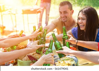Group of multiracial students having barbecue on sunny day - Young people cheering with beer in summer time on bbq - Concept about good and positive mood with friends - Focus on bottom center bottles