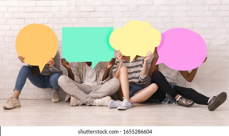 Group of multiracial teen friends covering faces with colorful speech bubbles over white brick wall, student community concept