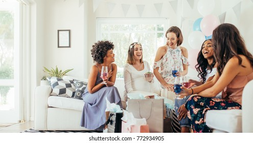 Group of multiracial women sitting together at a baby shower and having drinks. Young female friends having drinks at baby shower and laughing.