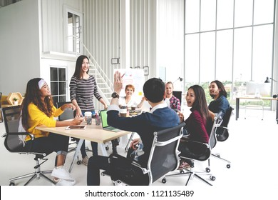Group of multiracial young creative team talking, laughing and brainstorming in meeting at modern office concept. Female standing and man raising hand for sharing while sitting together in rear view.