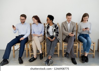 Group of multiracial young people entertain sitting in queue waiting using smartphones, diverse millennial employees communicate, chatting in line, busy with cellphones showing video or making selfie