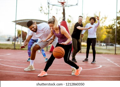 Group of multiracial young people   playing basketball  on court at outdoors