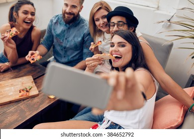 Group of multiracial young people taking a selfie while eating pizza. Young woman eating pizza her friends sitting around during a party.