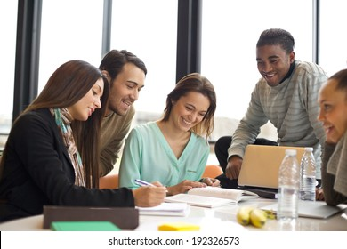 Group of multiracial young students studying together at a table. Mixed race people doing group study.