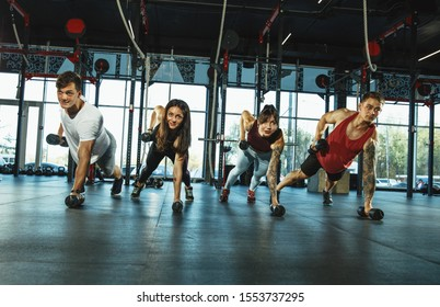 A group of muscular athletes doing workout at the gym. Gymnastics, training, fitness workout flexibility. Active and healthy lifestyle, youth, bodybuilding. Training in exercises with weights.