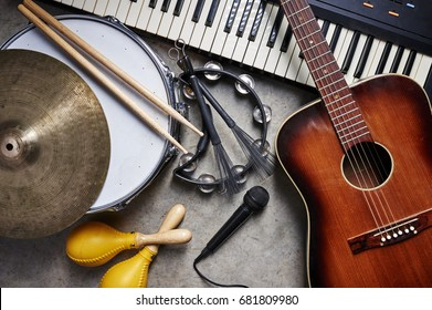 a group of musical instruments including a guitar, drum, keyboard, tambourine. - Shutterstock ID 681809980