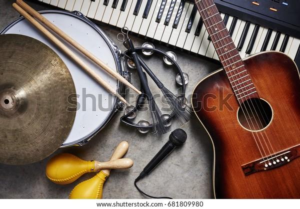 eine Gruppe von Musikinstrumenten wie Gitarre, Trommel, Tastatur, Tambourine.