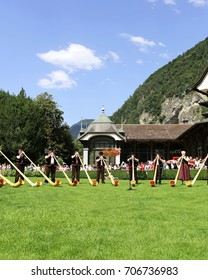 A group of musicians playing Alphorn dressed in traditional Swiss clothing, mountains in the background, celebrating Switzerland Day.  August 1, 2017, Interlaken, Switzerland.
